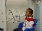 Child breathing into a machine during a lung function test