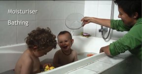 Mother pouring water over one of her 2 children having a bath