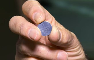 Photo of a button battery held in a hand