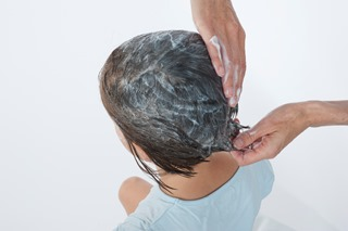 Applying conditioner to a child's hair