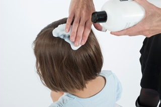 Applying hair conditioner to a child's hair