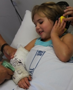 Photo of young girl having her arm plaster cast removed
