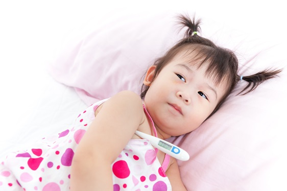 Little girl lying on sickbed with digital thermometer under her arm