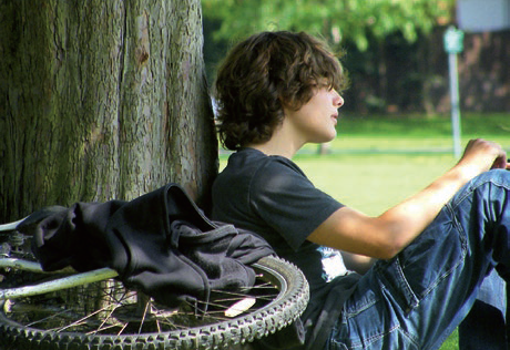 A teenage boy sitting against a tree