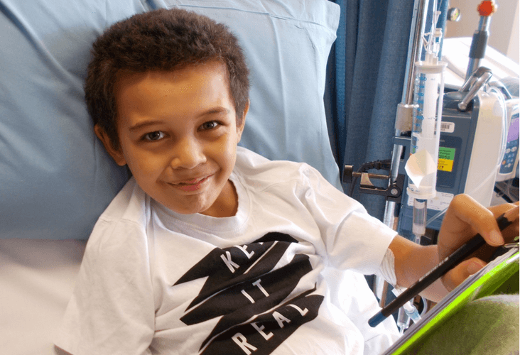 A boy in a hospital bed with a tablet