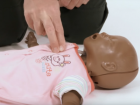 A person giving CPR to a baby mannequin