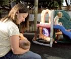 Mother breastfeeding her baby in a playground