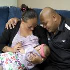 Mother breastfeeding her baby with baby's father looking on