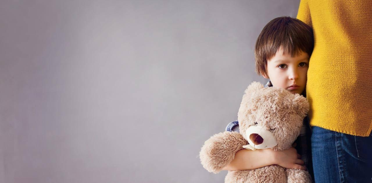 Photo of sad boy hugging his mother and his teddy bear