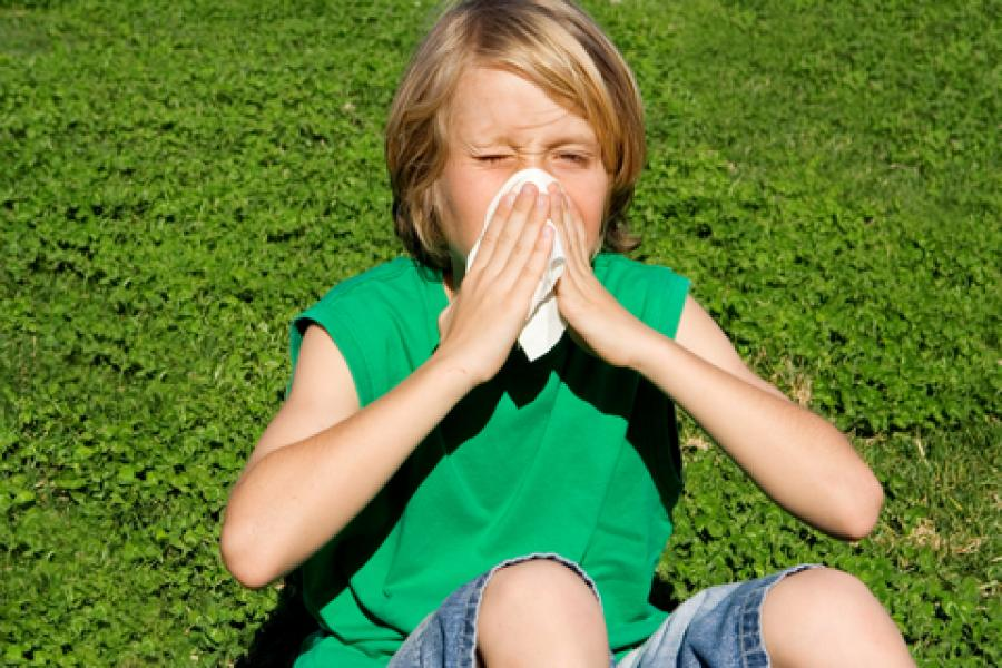 Child with allergy blowing nose