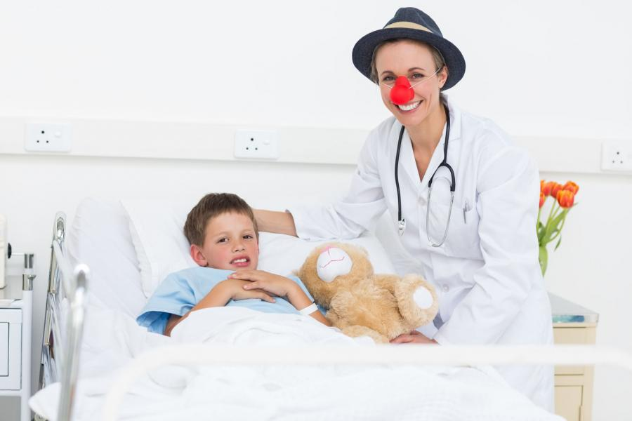 Young boy in a hospital bed with a teddy bear and a 'clown doctor' standing next to him