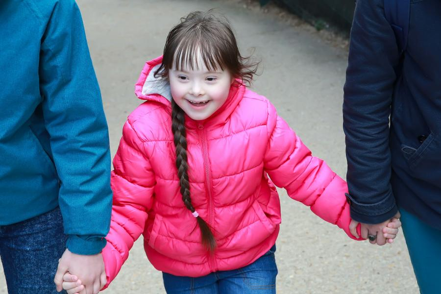Young girl with a disability holding her parents' arms on a walk