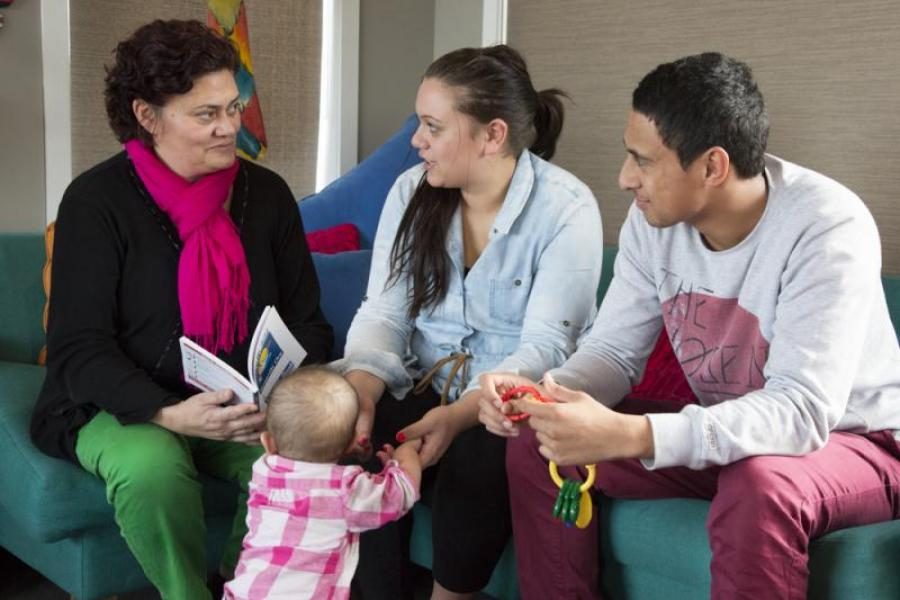 Well Child nurse talking to a young family (mother, father and baby) during a home visit