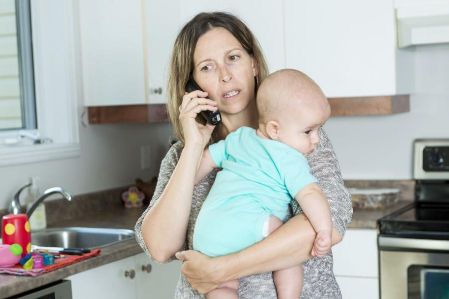 Mother on phone in kitchen holding her baby in her arms