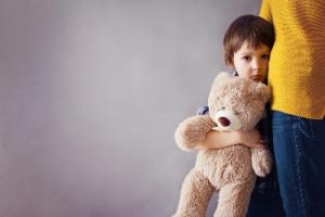 Little child, boy, hugging his mother and a teddy bear