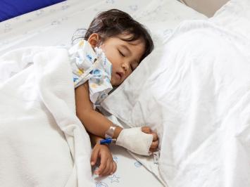 A sick child asleep on a hospital bed