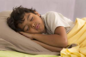 Young boy asleep in bed