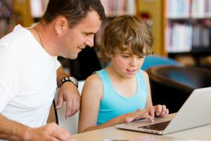 Boy on his computer with father sitting next to him and looking on
