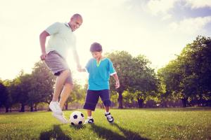 Father playing soccer with his son