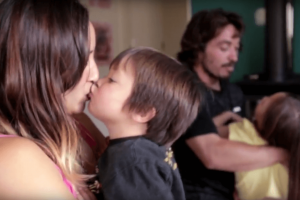 A mother kissing her young son while father and daughter play in the background