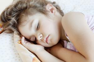 Close up of young girl asleep in bed