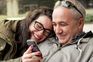 Father and teenage daughter looking and laughing at something on a mobile phone