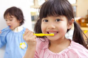 Young girl brushing her teeth with another child brushing teeth in the backgroud