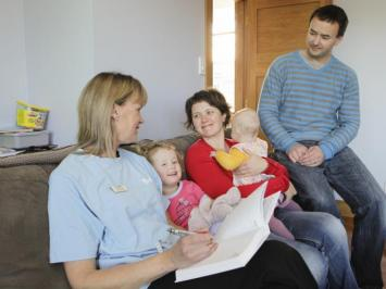 Well Child nurse sitting on a couch with a family (mother, father, baby and young child) during a home visit